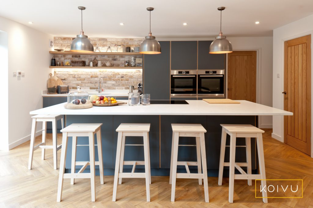 Planning your kitchen design layout. A dark grey plywood kitchen with island and exposed stonework.
