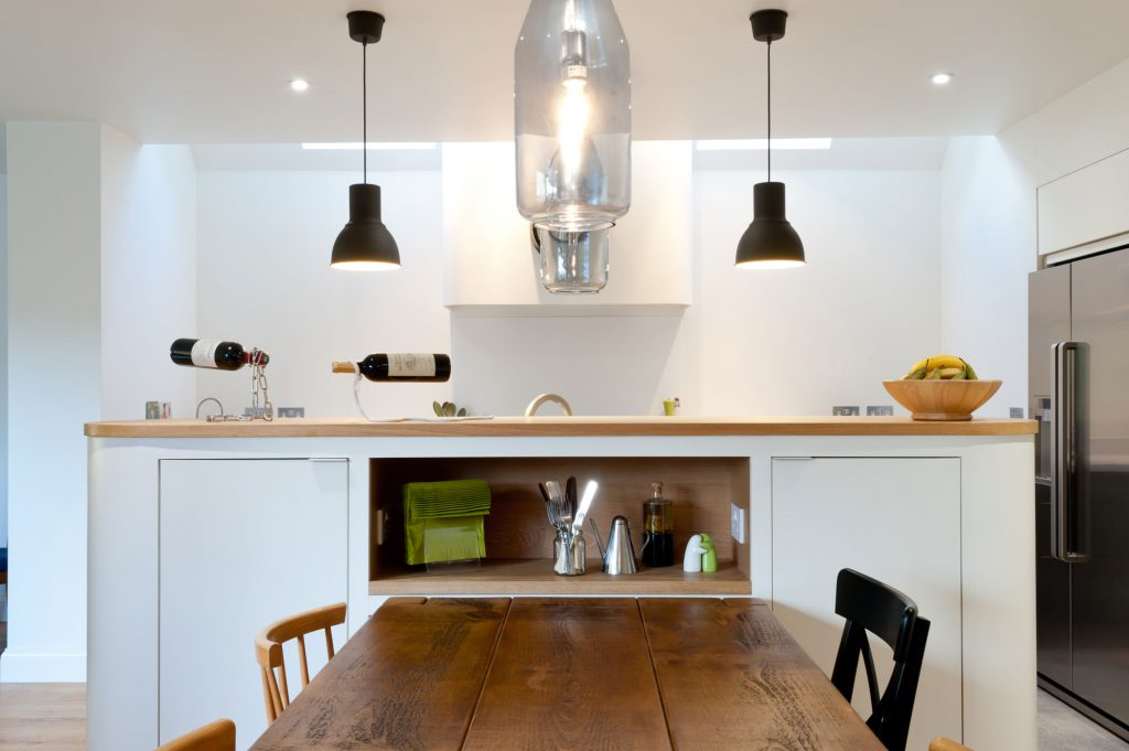 A white plywood kitchen with wooden worktop and accents - a bespoke kitchen built from scratch by the Koivu team.