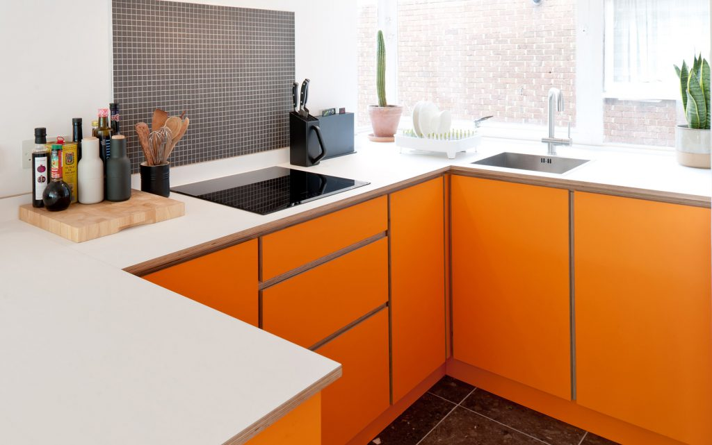 A small orange plywood kitchen with white worksurface - a bespoke kitchen created from scratch by the Koivu team.