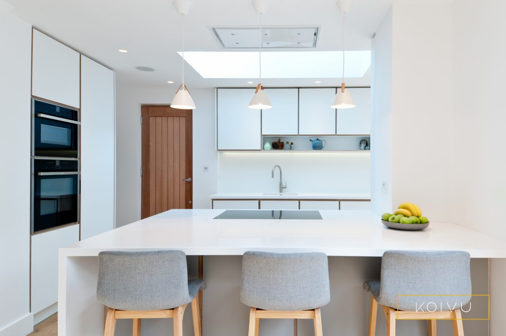 A white and grey plywood kitchen designed for a couple in Crystal Palace.