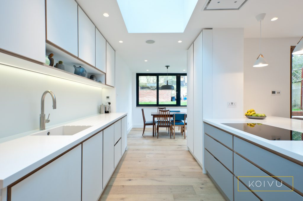 A white and grey plywood kitchen designed for a couple in Crystal Palace. Grey drawers in the island contrast with the bank of white wall units.