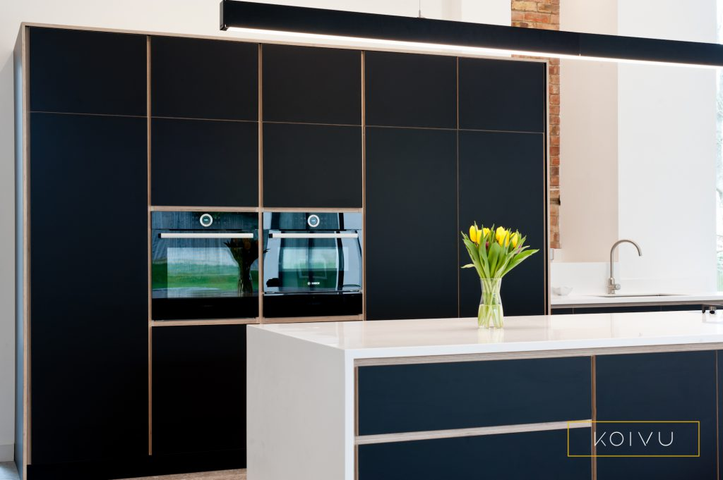 A black plywood kitchen fitted in Leatherhead by Koivu. A view of the full height units.