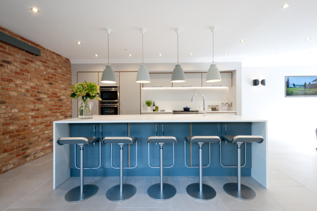 Plywood kitchen in blue and white with brick wall