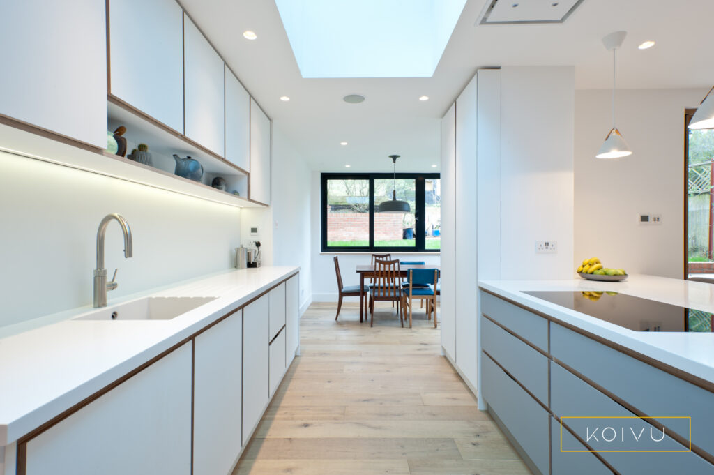Plywood kitchen in white and grey view of units towards dining area