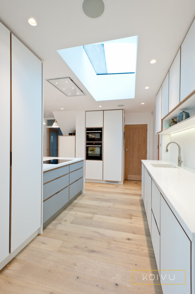 White plywood kitchen view with oak floor and roof light