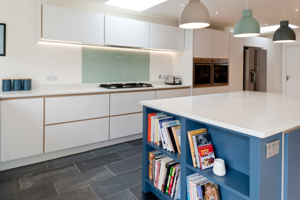 Plywood kitchen in white and blue with book shelves at the end of the island