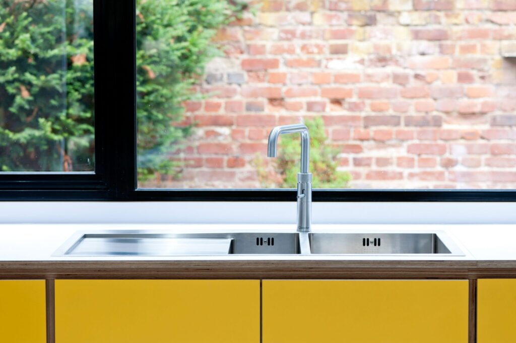 Tap over sink in front of window in spectrum yellow kitchen