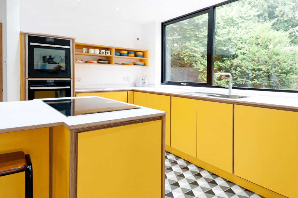 Yellow kitchen with monochrome accents and beautiful plywood detailing.