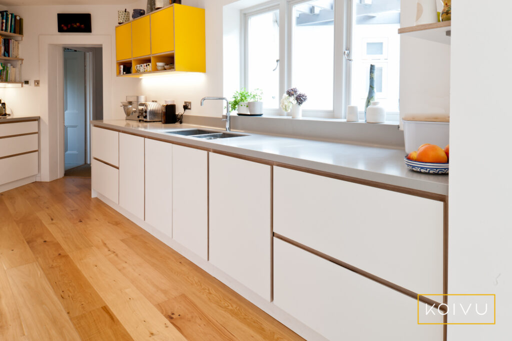 A bespoke design in an unusually shaped space. Yellow and white kitchen from Koivu.