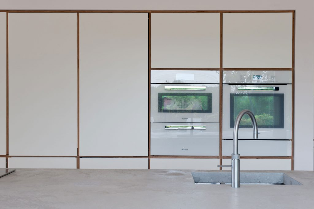 Hidden butler's cupboard in a white plywood kitchen designed by Koivu
