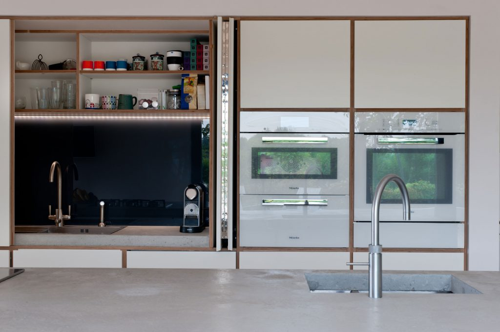 Butler's cupboard with doors open in a white plywood kitchen designed by Koivu.