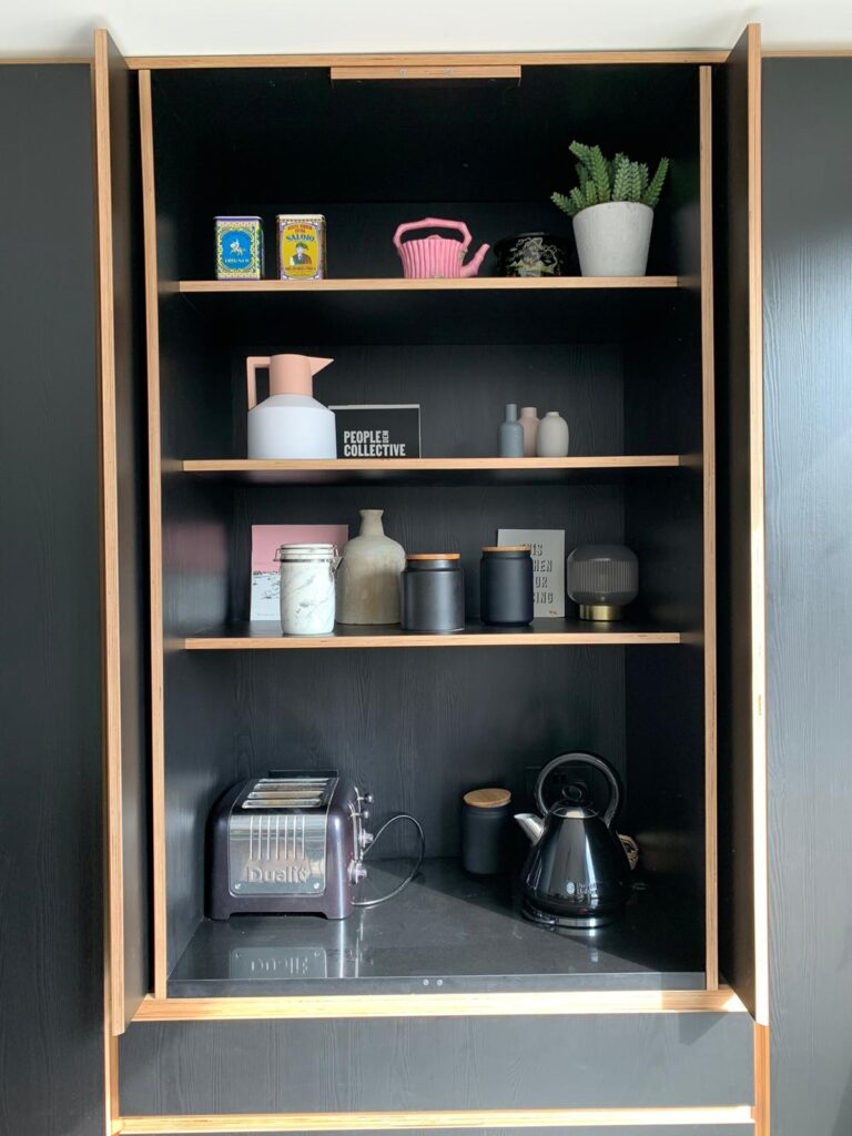 A picture of a bespoke designed black plywood Butler's Cupboard with pocket doors that have been opened up and folded back to create space.