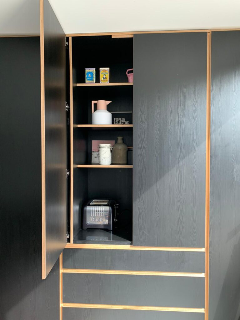 A picture of a bespoke designed black plywood Butler's Cupboard with one of the doors open to show the flexibility of the design